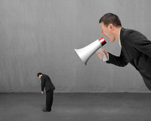 Businessman using megaphone yelling at his employee with concret