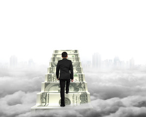 Businessman climbing the money stairs with gray cityscape clouds
