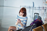 Young passenger at the airport, using her phone