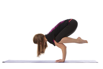 Studio shot of flexible woman doing yoga handstand