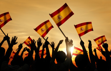 Silhouettes of People Holding Flag of Spain Concept