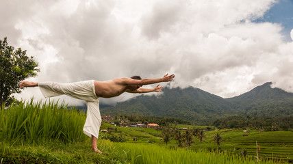 Man practicing yoga on the rice fields