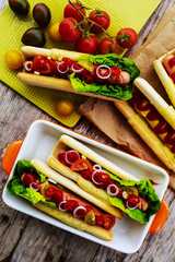 Grilled hot dogs with ketchup, mustard and relish on a table bac