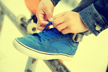 skateboarder hands tying shoelace on skatepark