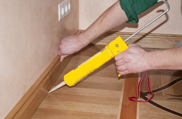 Carpenter on work putting wood parquet skirting board with glue