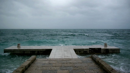 Rough weather at sea and waves crashing to the stone pier