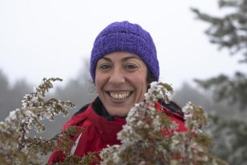 Mujer con gorro morado sonriendo en paisaje nevado