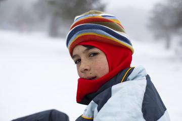 Niño con pasamontañas de colores en paisaje nevado