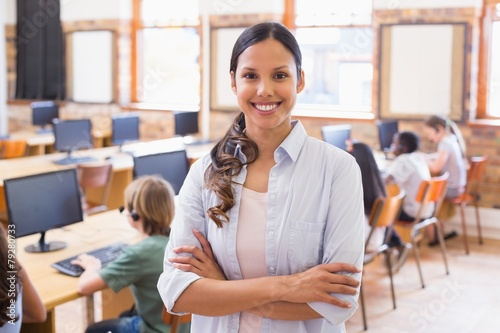 Pretty teacher smiling at camera at back of classroom - 79280733