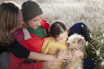 Familia en el campo abrazando a su perrillo