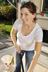 Frau wischt Boden mit Putzeimer und Aufnehmer