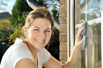 Frau putzt Fenster bei Frühjahrsputz