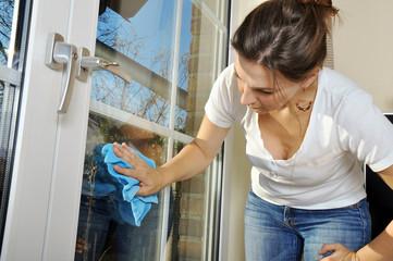 Frau wischt Fenster mit Scheibenklar