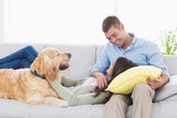 Couple with Golden Retriever on sofa poster