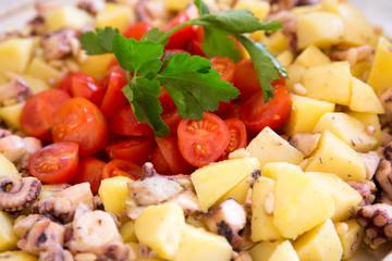 Pomodorini, polpo e patate in primo piano