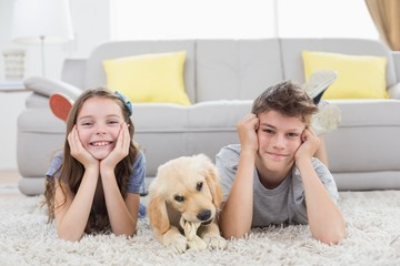 Happy siblings with puppy lying on rug