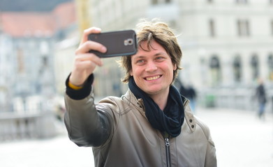 Young handsome hipster man making funny selfie in the city