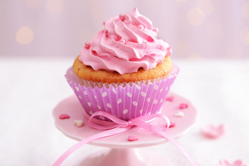 Sweet cupcake on table on light background