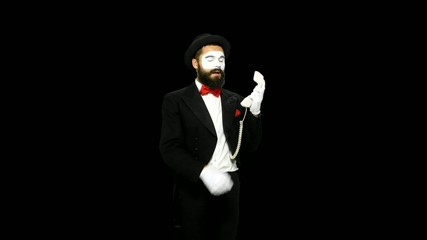 Man mime hears the ring of telephone and answers, alpha channel