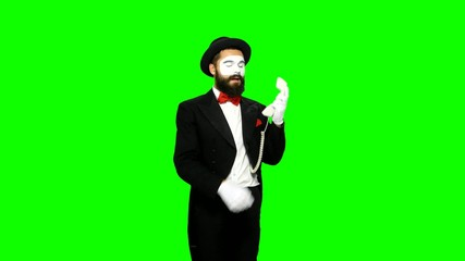Man mime hears the ring of telephone and answers on green screen