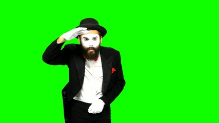 Man mime looks for something and uses binoculars on green screen