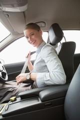 Businesswoman putting on her seat belt