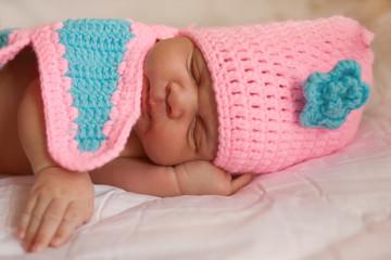Mulatto newborn baby sleeping wearing knitted