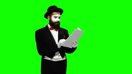 Unhappy man mime reads about something on paper, green screen