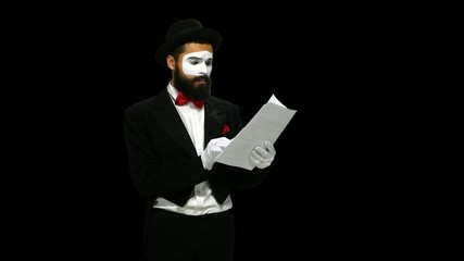 Unhappy man mime reads about something on paper, alpha channel