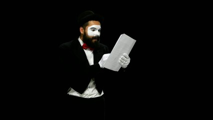 Happy man mime reads about something on paper, alpha channel