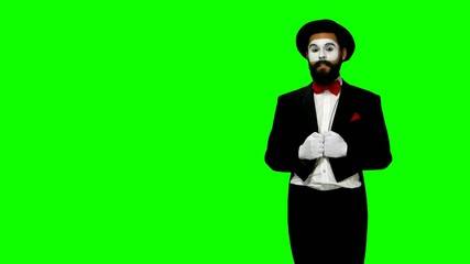 Man mime talks to somebody on green screen
