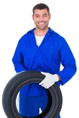 Mechanic holding tire on white background