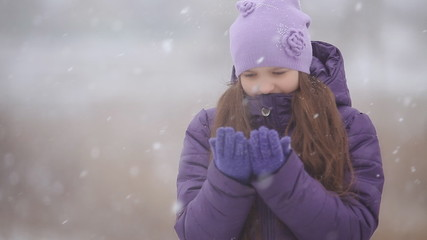 child in the snow warm breath hands CU