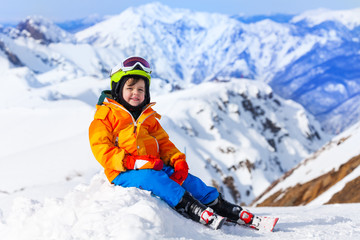 Sitting boy wearing ski mask and helmet in winter