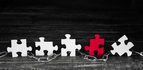 Ein rotes Puzzlestück unter weißen als Konzept Hintergrund