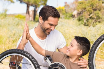 Father and son repairing bike together