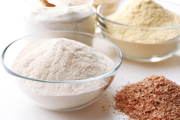 Different types of flour in bowls close up