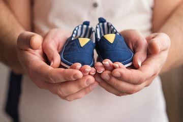 newborn shoes in  parents hands