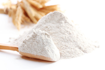 Heap of flour with wooden spoon and ears close up
