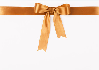Gold satin ribbon with a bow on a white background