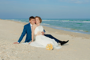 Young bride and groom on the beach in summer