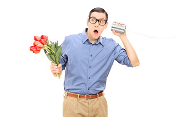 Man holding flowers and listening through tin can phone