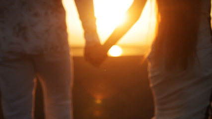 lovers go hand in hand at sunset