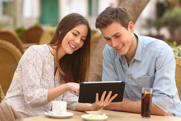 Couple watching media in a tablet in a restaurant