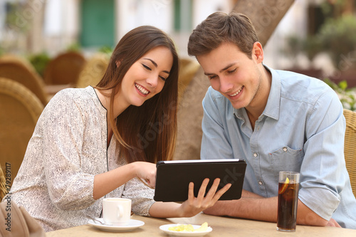 Couple watching media in a tablet in a restaurant - 79289117
