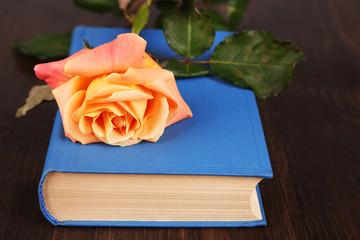 Beautiful rose with book on wooden table, closeup