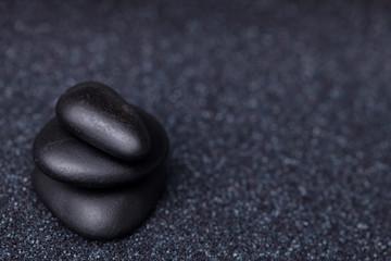 Balancing peaceful black stones in a relaxing zen garden