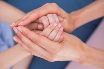 Mother and daughter touching hands