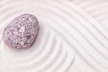 A limestone stone in the fine sand of the zen garden with wavy