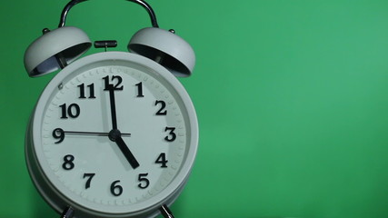 Ringing classical alarm clock at five o'clock green background